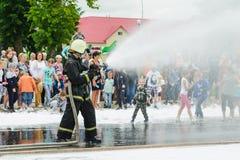 HORKI, BIELORRUSIA - 25 DE JULIO DE 2018: La salvación del rescate 112 del servicio vierte el agua de una manguera de bomberos du fotografía de archivo libre de regalías