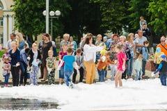 HORKI, BIELORRUSIA - 25 DE JULIO DE 2018: Los niños de diversas edades juegan con espuma blanca airosa en el día de fiesta del se foto de archivo libre de regalías