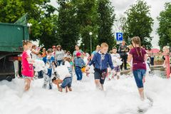 HORKI, BIELORRUSIA - 25 DE JULIO DE 2018: Los niños de diversas edades juegan con espuma blanca airosa en el día de fiesta del se imágenes de archivo libres de regalías