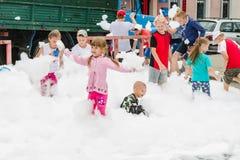 HORKI, BIELORRUSIA - 25 DE JULIO DE 2018: Los niños de diversas edades juegan con espuma blanca airosa en el día de fiesta del se fotos de archivo libres de regalías