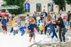 HORKI, BIELORRUSIA - 25 DE JULIO DE 2018: Los niños de diversas edades juegan con la espuma blanca en el parque en un partido en  foto de archivo libre de regalías
