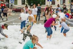 HORKI, BIELORRUSIA - 25 DE JULIO DE 2018: Los niños de diversas edades juegan con la espuma blanca en el parque en un partido en  fotos de archivo
