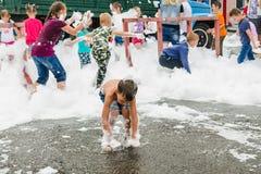 HORKI, BIELORRUSIA - 25 DE JULIO DE 2018: Los niños de diversas edades juegan con la espuma blanca en el parque en un partido en  foto de archivo