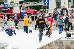 HORKI, BIELORUSSIA - 25 LUGLIO 2018: I bambini delle età differenti giocano con schiuma bianca nel parco ad un partito nel pomeri immagine stock