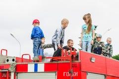 HORKI VITRYSSLAND - JULI 25, 2018: Barn av olik ålderlek på de röda bilarna av räddningstjänsten 112 på en ferie i parkerar royaltyfri bild