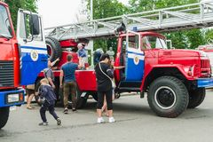 HORKI VITRYSSLAND - JULI 25, 2018: Barn av olik ålderlek på de röda bilarna av räddningstjänsten 112 på en ferie i parkerar royaltyfri foto