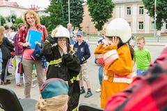 HORKI VITRYSSLAND - JULI 25, 2018: Barn av olika åldrar klär likformign av livräddare av service 112 på ett parti i parkerar mig arkivfoton