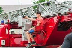HORKI VITRYSSLAND - JULI 25, 2018: En pojke tar en selfie på en röd bilräddningstjänst 112 på en ferie i parkerar på en sommardag royaltyfri foto