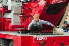 HORKI VITRYSSLAND - JULI 25, 2018: Pojken spelar på de röda bilarna av räddningstjänsten 112 på en ferie i parkerar royaltyfri bild