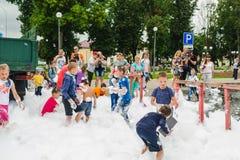 HORKI, WEISSRUSSLAND - 25. JULI 2018: Kinder des unterschiedlichen Alters spielen mit luftigem weißem Schaum am Feiertag des Rett lizenzfreie stockfotografie
