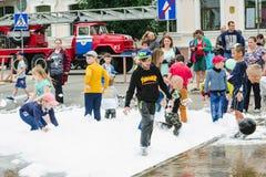 HORKI, WEISSRUSSLAND - 25. JULI 2018: Kinder des unterschiedlichen Alters spielen mit weißem Schaum im Park an einer Partei am Na stockbild