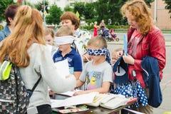 HORKI, WEISSRUSSLAND - 25. JULI 2018: Kleine Jungen mit verbundenen Augen zeichnen auf Papier auf einer Tabelle an einem Sommerta stockfotos