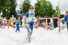 HORKI, WEISSRUSSLAND - 25. JULI 2018: Spiele eines wenig blonde Jungen mit luftigem weißem Schaum am Feiertag des Rettungsdiensts stockfotos