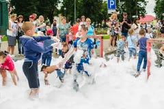 HORKI, WIT-RUSLAND - JULI 25, 2018: De kinderen van verschillende leeftijden spelen met een luchtig wit schuim bij de dienst 112  royalty-vrije stock fotografie