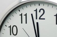Horloge analogue qui est proche de l'horloge de ` à 12h00 o Images libres de droits