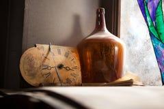 Horloge antique et la vieille bouteille près d'un mur de fenêtre images stock