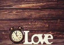 Horloge avec amour de mot Photographie stock
