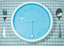 Horloge avec la cuillère et la fourchette Photographie stock