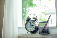 Horloge avec le crayon par la fenêtre photo stock