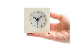 Horloge blanche d'isolement de place d'alarme de prise de main de femme sur le backg blanc Photographie stock libre de droits