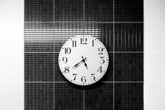 horloge blanche sur la surface noire et blanche Photographie stock libre de droits
