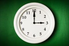 Horloge blanche sur un fond vert Images stock