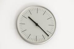 Horloge brillante argentée accrochant au mur Image libre de droits