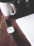 Horloge, ceramische camera, laptop op de houten lijst Stock Foto
