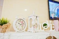 Horloge, chandelier et mots décoratifs d'amour sur le décor à la beauté Images libres de droits