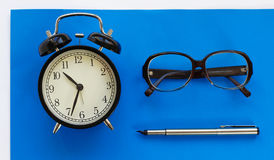 Horloge classique de bureau, stylo, verres sur un fond bleu Photos libres de droits