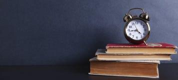Horloge d'alarme avec des livres images stock
