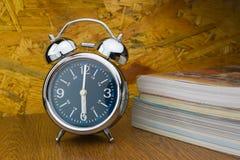 Horloge d'alarme avec des livres Photo stock