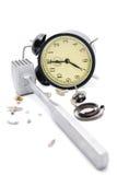 Horloge d'alarme cassée par un marteau. Isolat sur le blanc. Photos stock