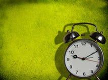 Horloge d'alarme contre le mur peint vert Images stock