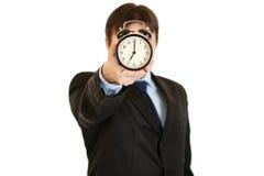 Horloge d'alarme de fixation d'homme d'affaires devant le visage Image libre de droits