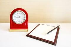 Horloge d'alarme et cahier avec le concept de crayon Image stock