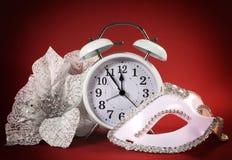 Horloge de bonne année, masque de partie de mascarade et fleurs blanches de fête Photographie stock libre de droits