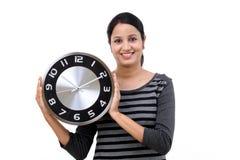 Horloge de bureau de fixation de jeune femme photos stock