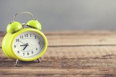 Horloge de cru sur la table en bois et le fond gris de mur photo stock