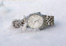 Horloge de main en métal se situant dans la neige Image libre de droits