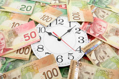 Horloge de mur et dollars canadiens Photographie stock libre de droits