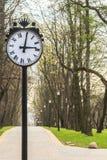 Horloge de parc sur le fond d'allée de ressort Photos stock