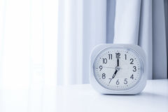 Horloge de place blanche sur le support blanc de lit avec le fond blanc de rideau, temps de matin dans la décoration minimale de  Images stock