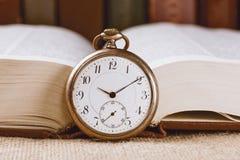 Horloge de poche de vintage sur le livre sur le fond de livres image libre de droits