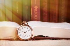 Horloge de poche de vintage sur le livre sur le fond de livres avec le faisceau de lumière images libres de droits