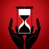 Horloge de sable avec à disposition Photo stock