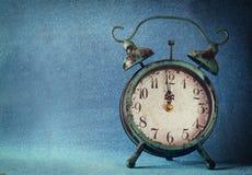 Horloge de vintage au-dessus de fond bleu de bokeh de glace Concept d'an neuf Foyer sélectif Photographie stock