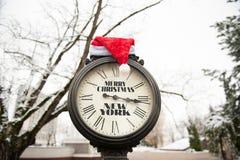 Horloge de vintage avec le chapeau de Joyeux Noël New York et de Santa Claus de titre sur eux extérieurs en hiver Photos libres de droits