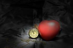 Horloge de vintage et coeur rouge sur le fond noir, le concept d'amour et de temps dans la photographie immobile de la vie Photos stock