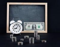 Horloge de vintage, tableau noir, billet d'un dollar, et tours de pièce sur le noir Photos libres de droits